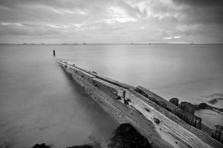 Small wooden breakwater juts out into the calm sea on an overcast day.  Black and white.