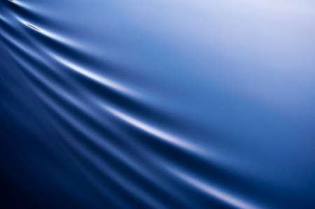 Beautiful, calm blue water is broken by elegant, diagonal ripples with lots of copy space. Stock Photo