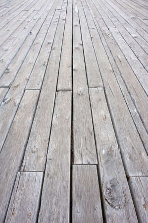 Old, weathered, grey wooden deck stretching into the distance. Stock Photo