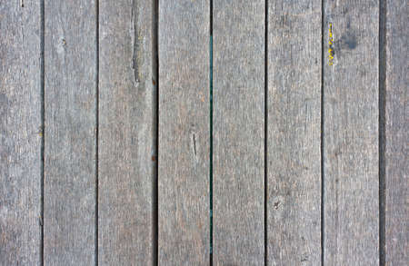 Looking down on an old, weathered, grey wooden deck.  Wood texture background.