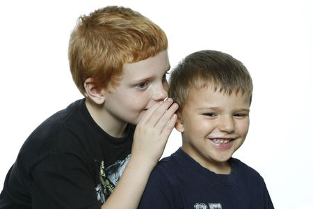 Two young toddler boys telling a secret, one boy is laughing. photo