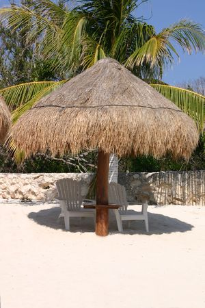 palapa: Palapa Hut on the beach with abandoned chairs. Stock Photo