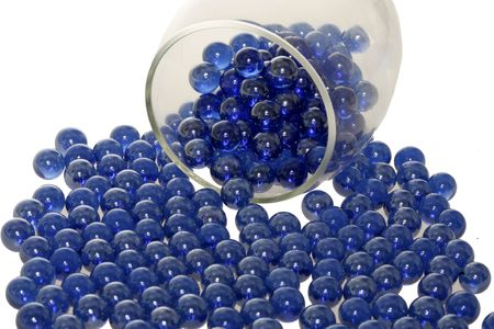 falling out: Blue marbles falling out of a glass. Stock Photo