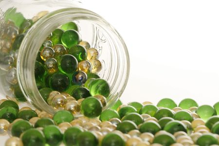liesure: Green and Gold marbles spilling out of a jar. Stock Photo