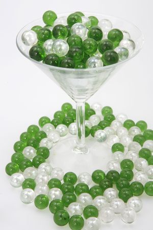 liesure: Green and Clear marbles resting in a martini glass with some spilled on the ground.