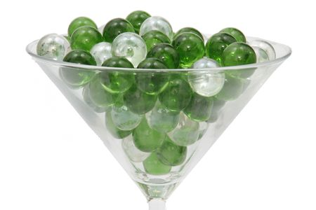 liesure: Green and Clear marbles resting in a martini glass.