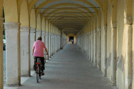 go ahead: image of the old arcades of Comacchio with people who cycle, also it means go ahead, although with difficulty, and reach instill