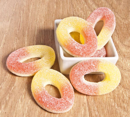 gummie: colorful circular jelly candies on plate, on  wooden board Stock Photo