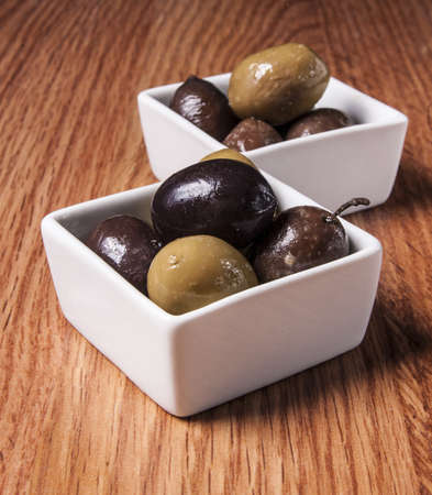 Fresh olives in a white bowl, on wooden background  photo