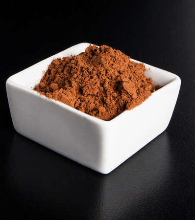 Cacao powder on white bowl, on black background photo