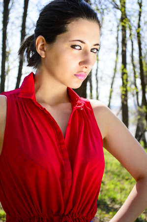 Young beautiful woman in red dress in woods photo