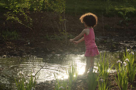 yard stick: Little cute girl playing with stick in small pond