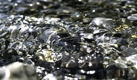 Silver and golden reflections on the water surface, smooth gold and blue background with circular patterns. Perfect background image. Stones on the backdrop