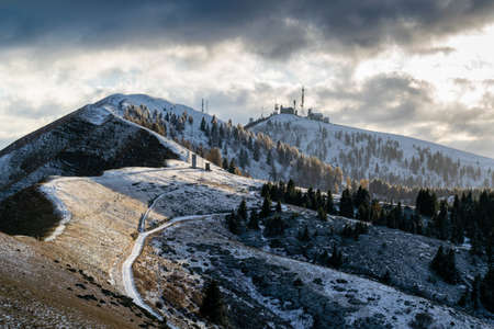 Snowy mountain landscape at sunset. The sun's rays break through the clouds. Alpe del Nevegal, Belluno, Italy