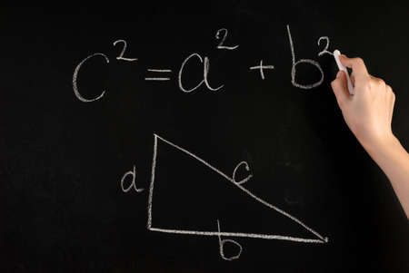 Girl hand write Pythagoras Theorem and angled triangle with on school blackboard with white chalk