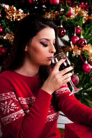 Cute girl in red sweater drinking red wine and Christmas tree in background. Xmas and New Year holiday concept Stockfoto