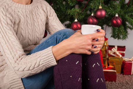 Young Woman in sweater holding cup of coffee on knees and Christmas tree and present boxes in background, close up