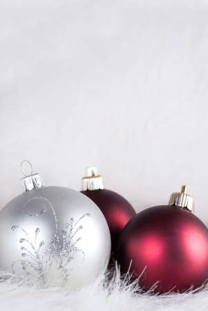 Christmas decorations on a puffy white fur, red and white, close up and space for text. Xmas and New Year holiday concept.