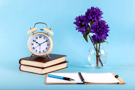 Open notebook with a pen, old clock on books and flowers in a vase on a blue background, blog concept image Stock Photo