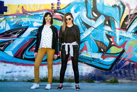 Twee mooie meisjes die op een de lentedag stellen voor graffiti op de muur op achtergrond