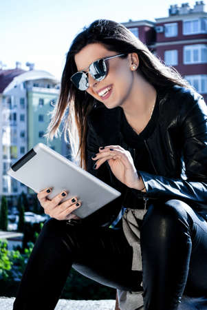 Happy girl with tablet in spring day outside surfing on Internet