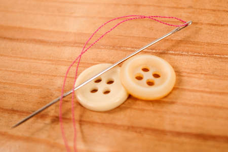 Sewing needle with thread and cloth buttons on wooden background Stock Photo
