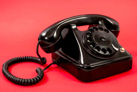Old black phone isolated on a red background Stock Photo