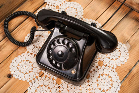 Old black phone on lace tablecloths and wooden background