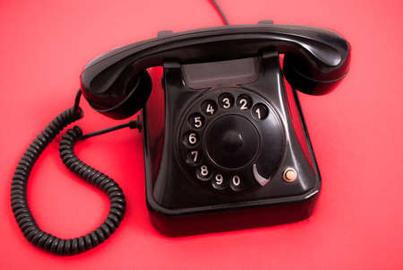 Old phone with dials on red background Stock Photo