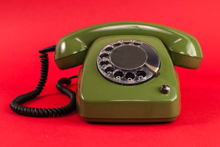 赤の背景に古いレトロな緑の携帯電話