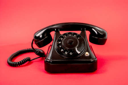 Retro black phone isolated on a red background Stock Photo
