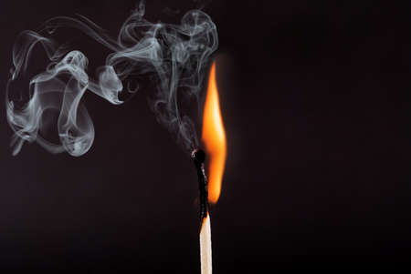 Matches stick with the flame and smoke burning, isolated on a black background Banque d'images
