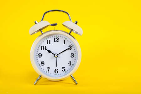 Old clock on yellow background and space for text