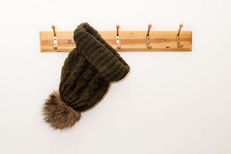 Winter wool cap with a furry ball in green color hanging on a hat stand on white background