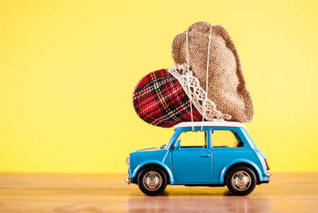 Miniature toy car carrying retro heart on yellow background