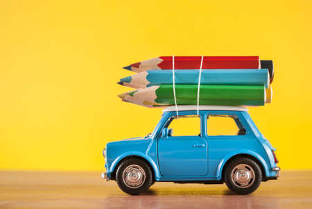 Miniature figure toy car Mini Morris carrying colored pencils on roof on yellow background in studio. Education and art concept.