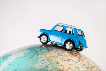 NIS, SERBIA - JANUARY 8 2018 Miniature figure toy car Mini Morris on geographical globe of earth on white background in studio. Travel concept.