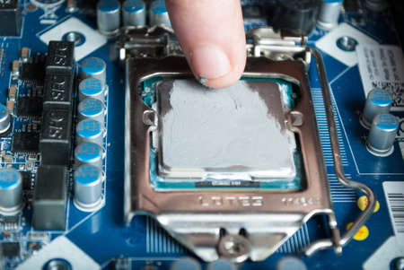 NIS, SERBIA - MARCH 10 2018: Applying thermal paste with finger during Processor Intel i5 installation on motherboard. Close up, selective focus Editorial