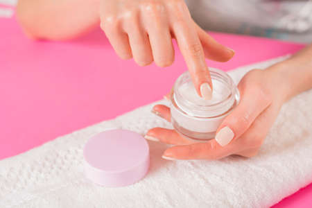 Woman finger touching open cream for hands on white towel and pink desk. Manicure and Hand beauty concept. Close up, selective focus