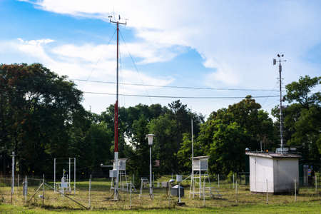 Weather station for monitoring ambient air pressure, humidity, wind vane and temperature in the forest and meadow in nature. Meteorology concept image