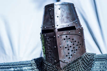 Medieval old knight helmet and chain mail for protection in battle. Very heavy headdress on stand. Middle ages armor concept