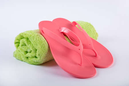 Pink sandal flip flop on green towel and white background. Summer vacations concept, close up