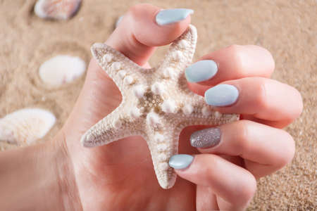 Girl with blue manicure nails polish holding starfish in hand and sandy sea beach in background. Summer vacation and female beauty concept. Close up, selective focus