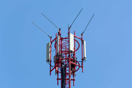 Close up of Telecommunication tower with red antennas with blue sky. Mobile phone communication equipment concept.