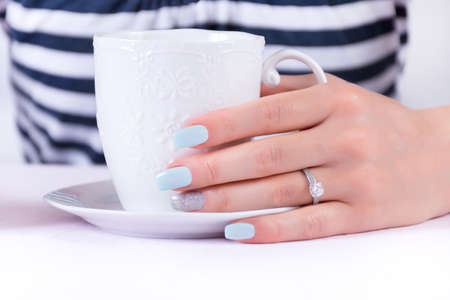 Girl hand with blue manicure nails polish and diamonds engagement ring holding cup of coffee in sailor t-shirt in background. Summer and vacation concept. Close up, selective focus Фото со стока