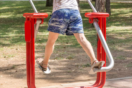Female legs does exercises at simulator in park on sunny summer day. Fitness and gym concept. Close up, selective focus