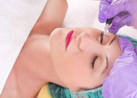 Cosmetologo che fa trucco permanente eyeliner sulla bella ragazza in studio di bellezza. Tattooist rendendo eyeliner con strumento e guanto protettivo. Primo piano, messa a fuoco selettiva
