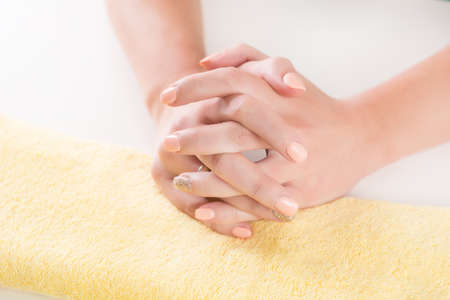 Young female hand with orange manicure on nails crossed fingers on yellow towel in beauty studio. Fashion and manicure concept. Close up, selective focus Stockfoto