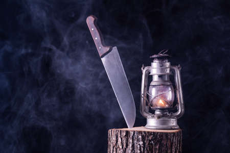 Big knife and burning old oil lamp on wood log in forest and black foggy background. Horror and Halloween concept Imagens