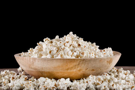 Popcorn in retro wooden bowl and spilled on wooden desk and black background. Food concept. Close up, selective focus